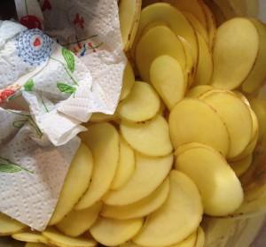 Kartoffelscheiben in der Salatschleuder trocknen und danach mit Küchenpapier vollends trocknen